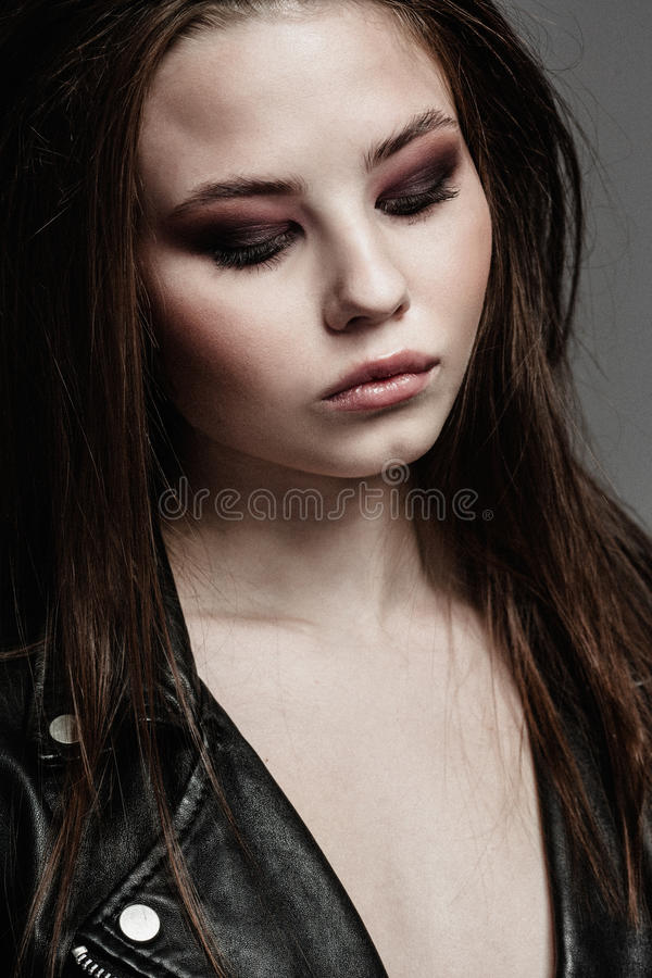 Beautiful woman portrait in rock style. Smoky eyes makeup royalty free stock photo