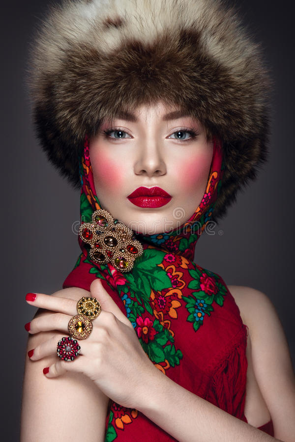 Beautiful woman portrait in russian style with fur hat and scarf stock image