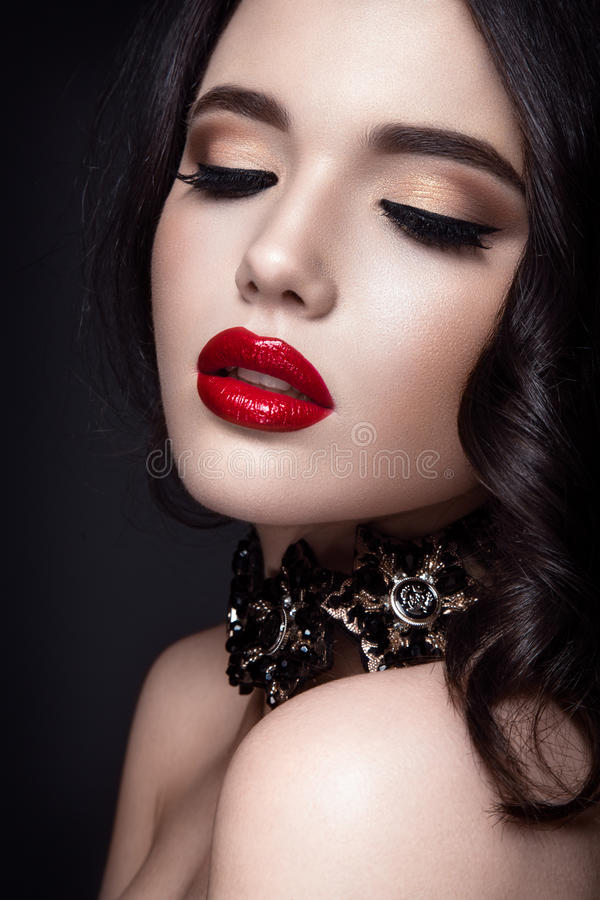 Beautiful woman portrait. Young lady posing close up on black background. Glamour make up, red lipstick. Gorgeous jewelry on neck stock image