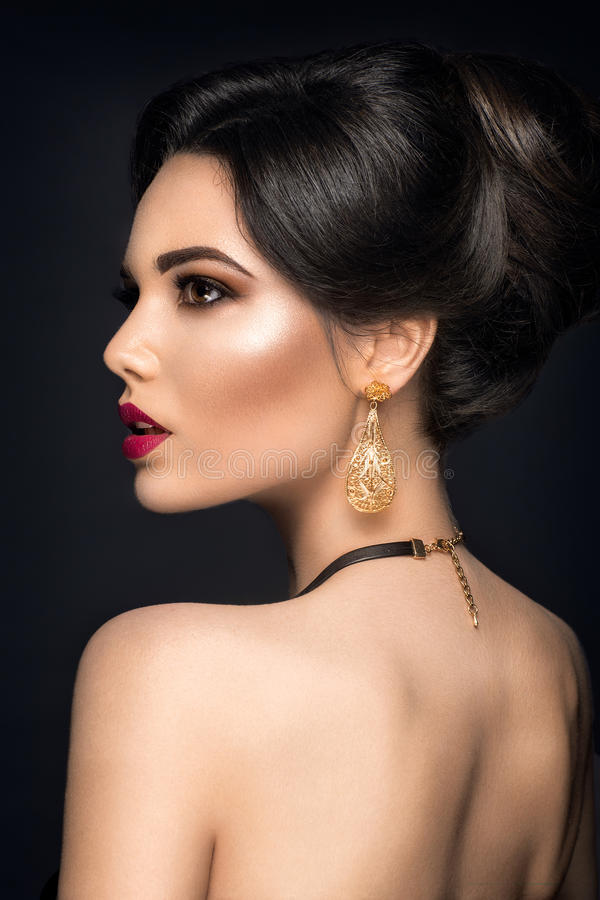 Beautiful woman portrait. Young lady posing with gold jewelry. Model isolated on black background. Golden eyeshadow and nails stock images