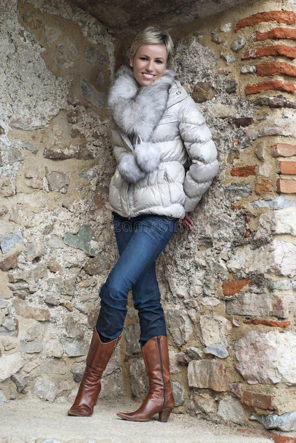 Beautiful woman posing in brick niche. Beautiful smiling woman posing in brick niche stock image