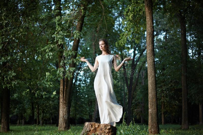 Beautiful Woman Posing like Goddess in White Long Dress at Nature. Boho Style, Soul Calm, Wellness. Freedom and Relaxing. Beautiful Woman Posing like Goddess in royalty free stock photos