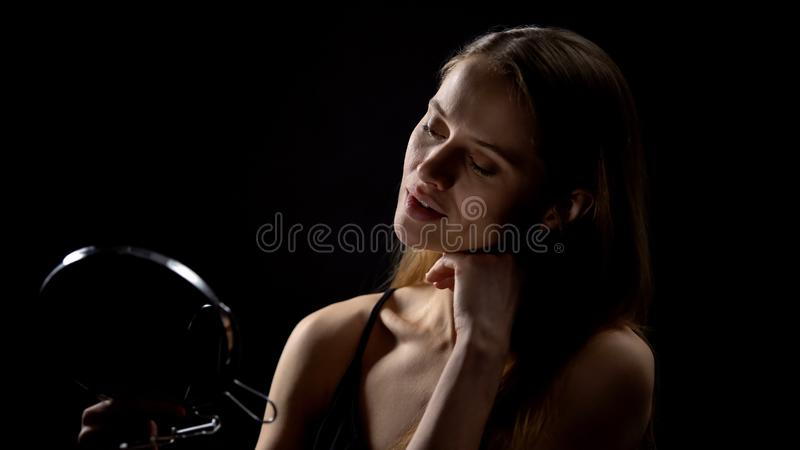 Beautiful woman posing for mirror against dark background, enjoying reflection. Stock photo royalty free stock image