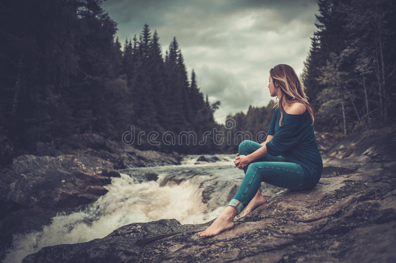 Beautiful woman posing near waterfall with mountain forest on the background. royalty free stock photos