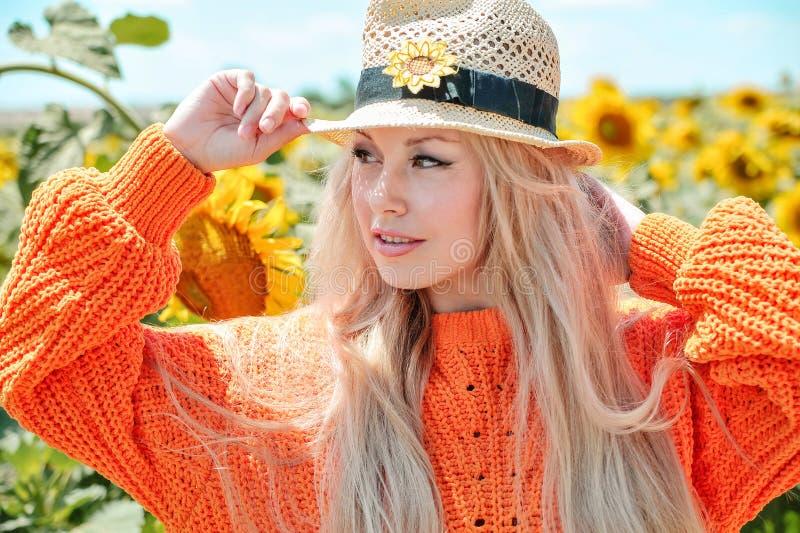 Beautiful woman posing in orange sweater on meadow with sunflowers. stock photo