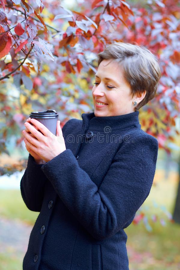 Beautiful woman posing with paper cup of tea or coffee in autumn city park, fall season royalty free stock photography