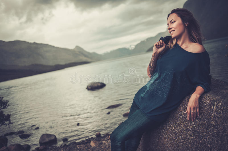 Beautiful woman posing on the shore of a wild lake, with mountains on the background. stock photography