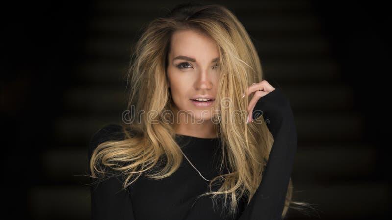 Beautiful woman posing in studio on dark background royalty free stock image
