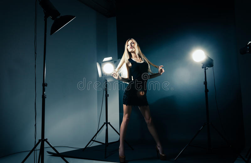 Beautiful woman posing at studio in light flashes. Beautiful female model posing at studio in the light flashes stock photography