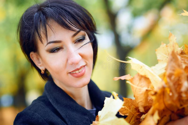 Beautiful woman posing with yellow leaves in autumn city park, fall season royalty free stock photography