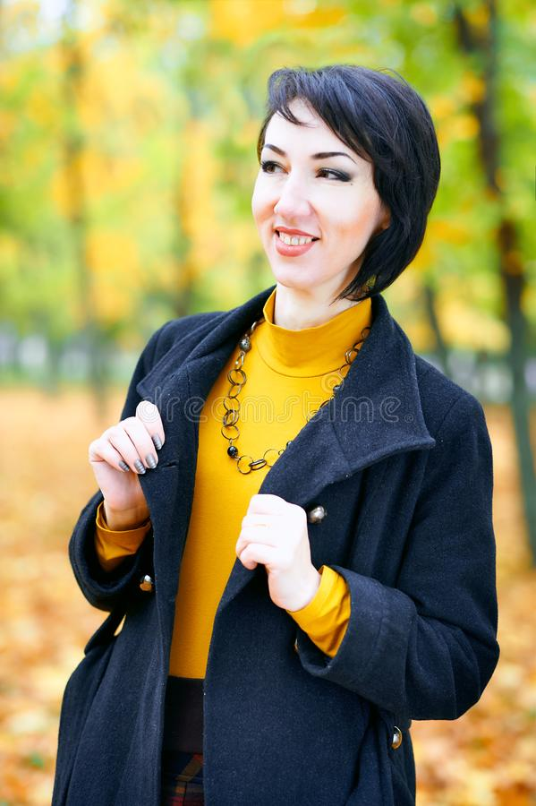 Beautiful woman posing with yellow leaves in autumn city park, fall season stock photos
