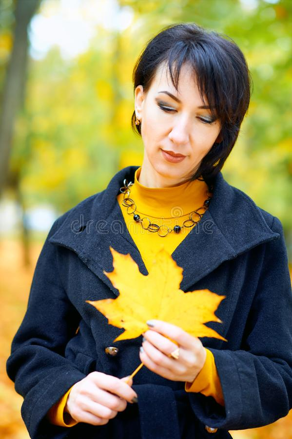 Beautiful woman posing with yellow leaves in autumn city park, fall season stock photo