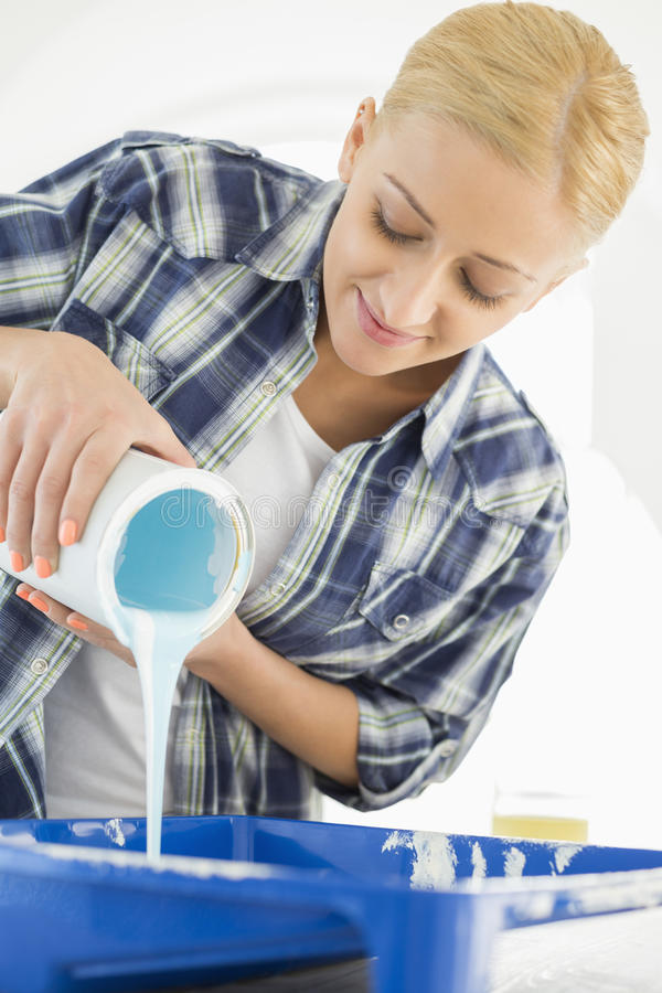 Beautiful woman pouring paint in container royalty free stock images