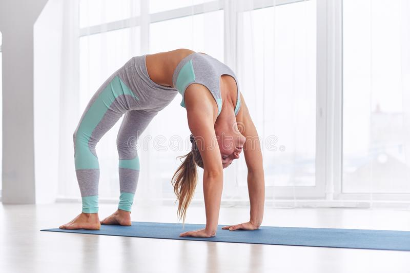 Beautiful woman practices backbend yoga asana Urdhva Dhanurasana - Upward facing bow pose at the yoga studio. Beautiful woman practices backbend yoga asana stock images