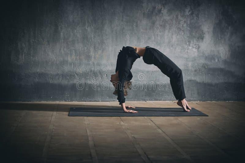 Beautiful woman practices backbend yoga asana Urdhva Dhanurasana - Upward facing bow pose in the dark hall.  royalty free stock images