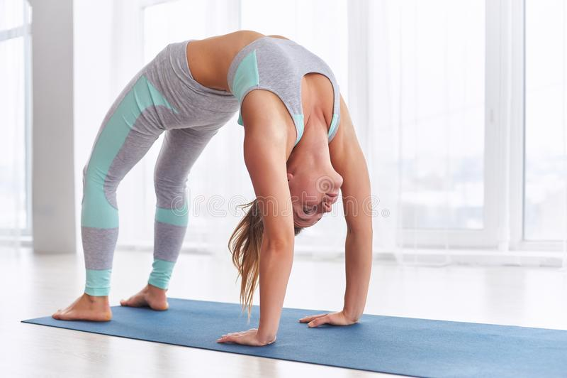 Beautiful woman practices backbend yoga asana Urdhva Dhanurasana - Upward facing bow pose at the yoga studio. Beautiful woman practices backbend yoga asana royalty free stock photography