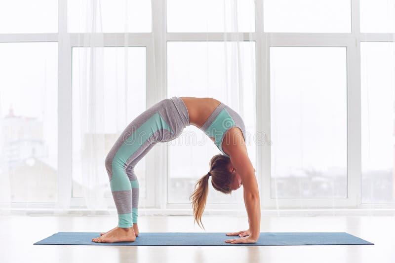 Beautiful woman practices backbend yoga asana Urdhva Dhanurasana - Upward facing bow pose at the yoga studio. Beautiful woman practices backbend yoga asana stock image