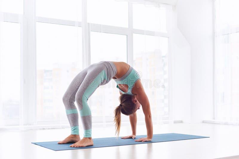 Beautiful woman practices backbend yoga asana Urdhva Dhanurasana - Upward facing bow pose at the yoga studio. Beautiful woman practices backbend yoga asana stock photos