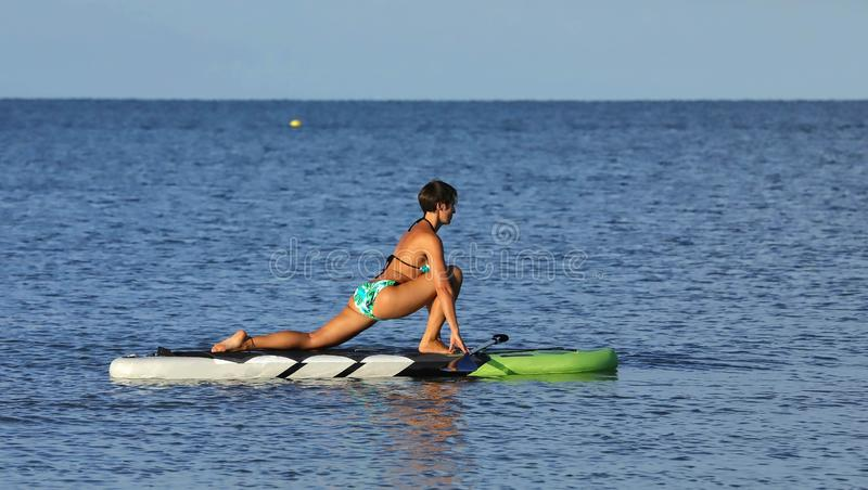 Beautiful woman practices yoga on a stand up paddle board. royalty free stock images