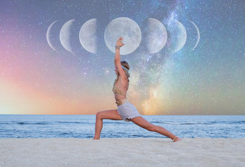 Beautiful woman is practicing yoga on the beach on Milky Way background stock image