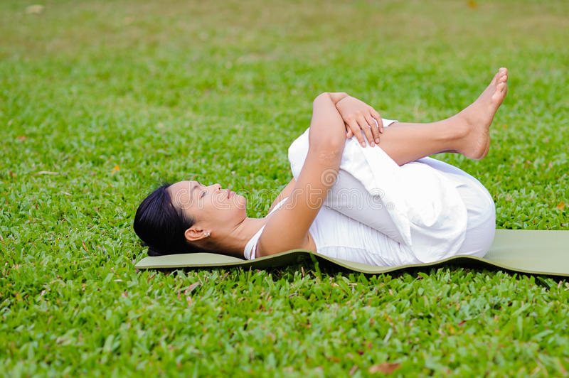 Beautiful woman practicing yoga in the park royalty free stock image