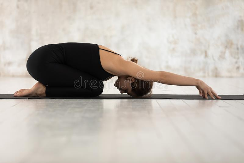 Beautiful woman practicing yoga, relaxing in Child pose, Balasana exercise stock photography
