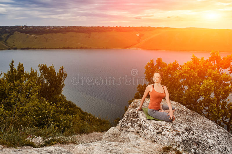 Beautiful woman is practicing yoga on the rock above big river against sky. stock photography