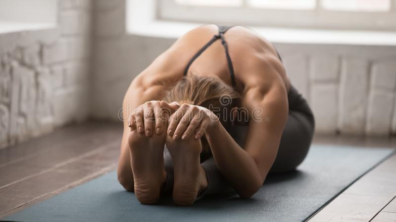 Beautiful woman practicing yoga, Seated forward bend pose, paschimottanasana stock photo