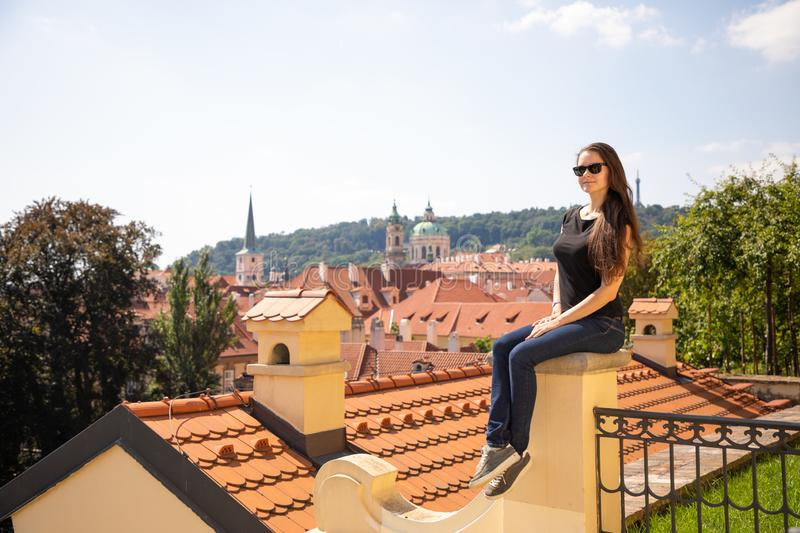 Beautiful woman in Prague city background over red roofs in Prague, Czech Republic royalty free stock photo