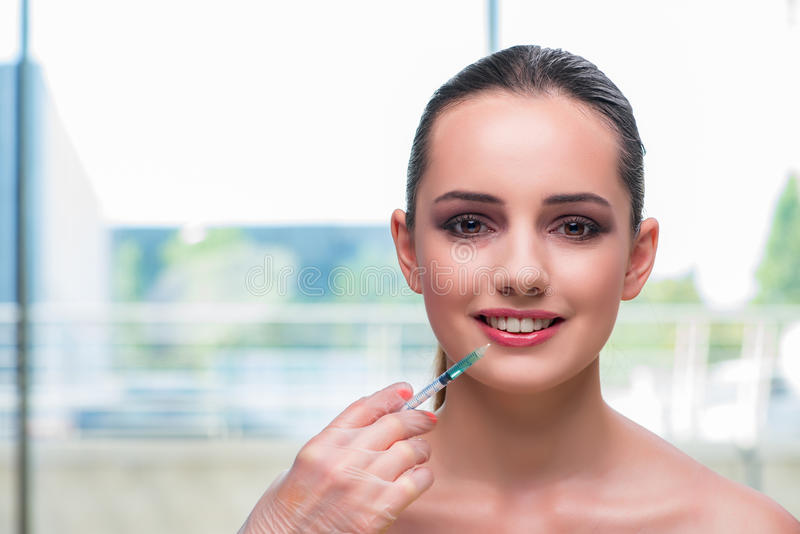 The beautiful woman preparing for botox injection stock photography