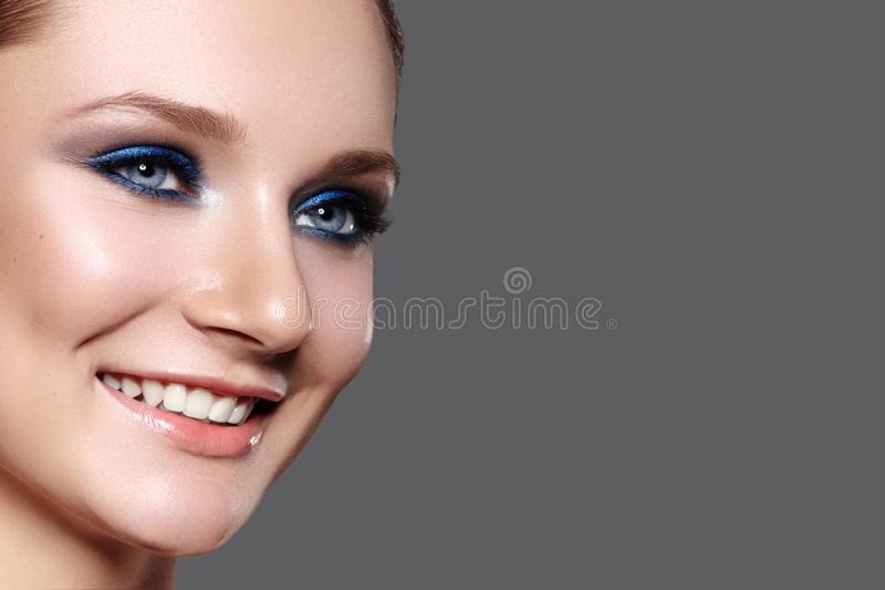 Beautiful Woman with Professional Blue Makeup. Celebrate Style Eye Make-up and Shine Skin. Smiling Fashion Model stock photography