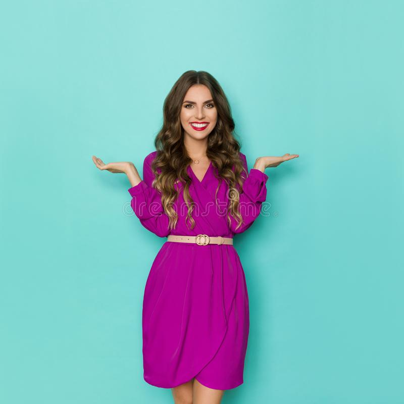 Beautiful Woman In Purple Dress Is Standing With Hands Raised And Smiling stock photos