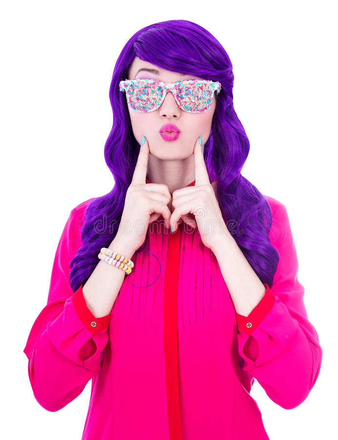 Beautiful woman with purple hair and glasses with sugar candies. Isolated on white background royalty free stock photography