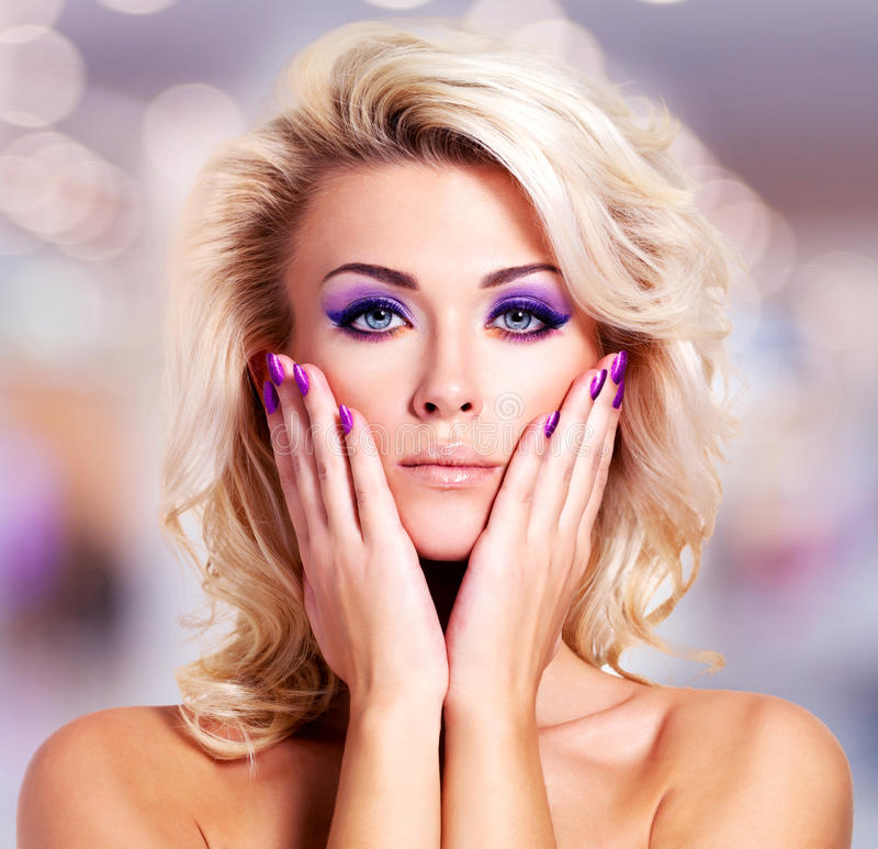 Beautiful woman with purple nails and glamour makeup. Beautiful woman with purple nails and bright glamour makeup royalty free stock images