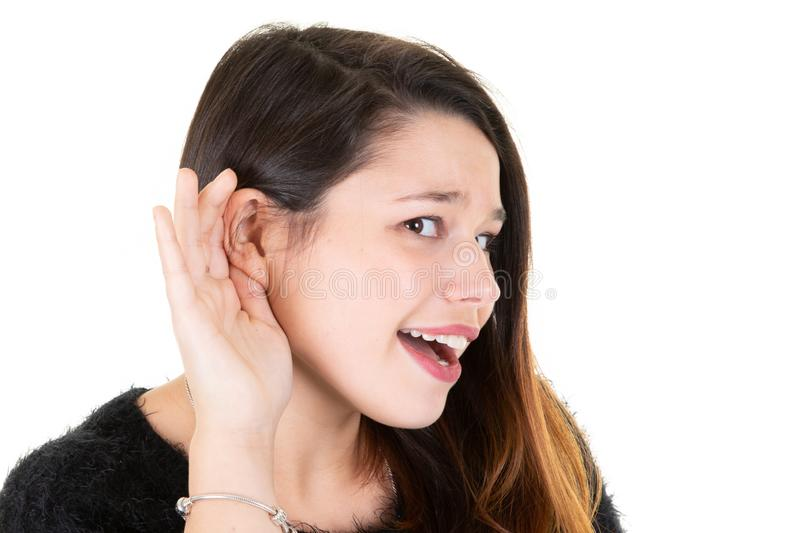 Beautiful woman puts hand to ear to hear better Young girl listening something over white background. A Beautiful woman puts hand to ear to hear better Young royalty free stock photos