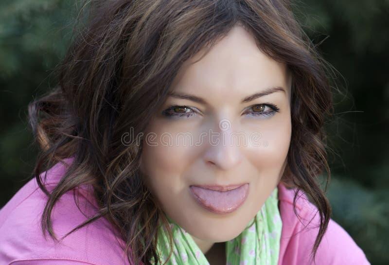Beautiful woman puts out tongue stock photos
