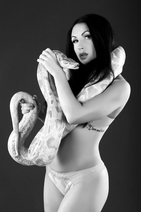 Beautiful woman with python. Black & white, monochrome vintage photo, one person is holding wild albino python. Erotic emotional atmosphere, passion, desire royalty free stock photography