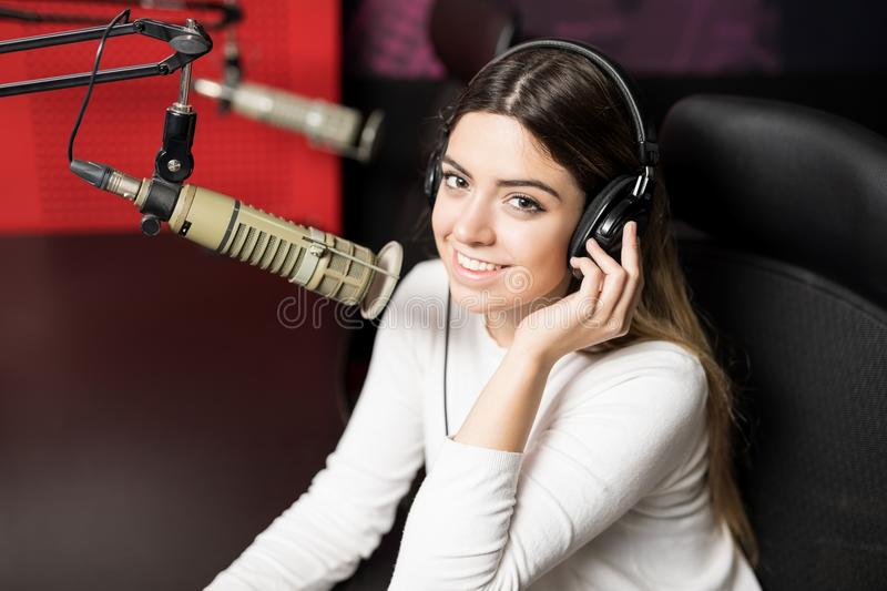 Beautiful woman radio broadcaster. Close up of a beautiful woman radio broadcaster with headphones talking in mic with a smile on her face at radio station stock images