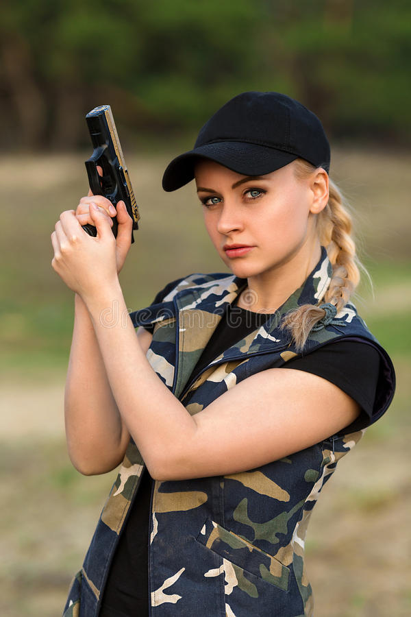Beautiful woman ranger with gun in camouflage. Portrait of beautiful blonde woman ranger in camouflage and with rifle on the forest background stock image