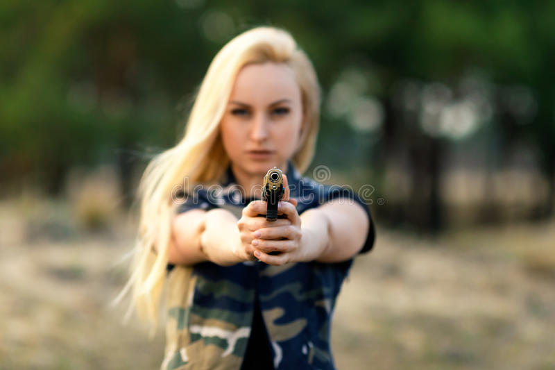 Beautiful woman ranger with gun. Portrait of beautiful blonde woman ranger in camouflage and with gun - defocused image with shallow depth of field royalty free stock image