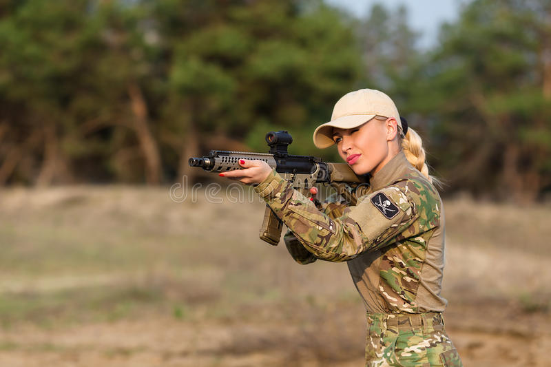 Beautiful woman ranger with rifle in camouflage. Portrait of beautiful blonde woman ranger in camouflage and with rifle on the forest background stock photos