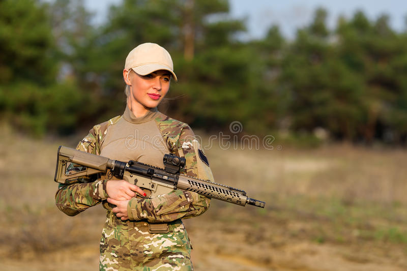 Beautiful woman ranger with rifle in camouflage. Portrait of beautiful blonde woman ranger in camouflage and with rifle on the forest background royalty free stock photos
