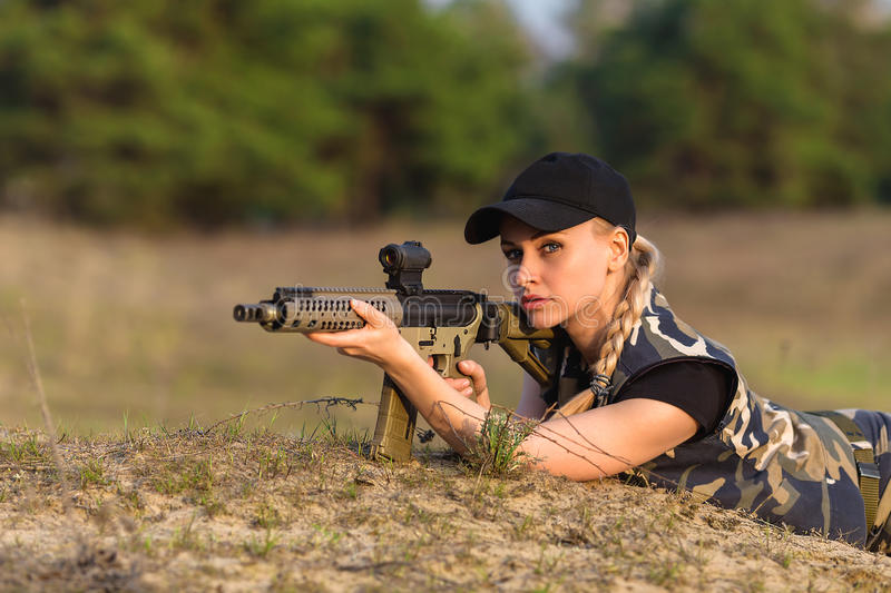 Beautiful woman ranger with rifle in camouflage. Portrait of beautiful blonde woman ranger in camouflage and with rifle on the forest background royalty free stock image