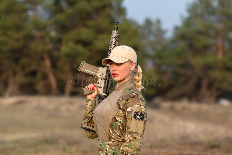 Beautiful woman ranger with rifle in camouflage. Portrait of beautiful blonde woman ranger in camouflage and with rifle on the forest background royalty free stock photography