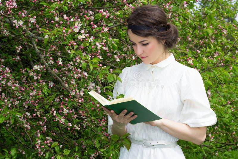 Beautiful woman reading book in blooming spring garden. Young beautiful woman reading book in blooming spring garden royalty free stock photos