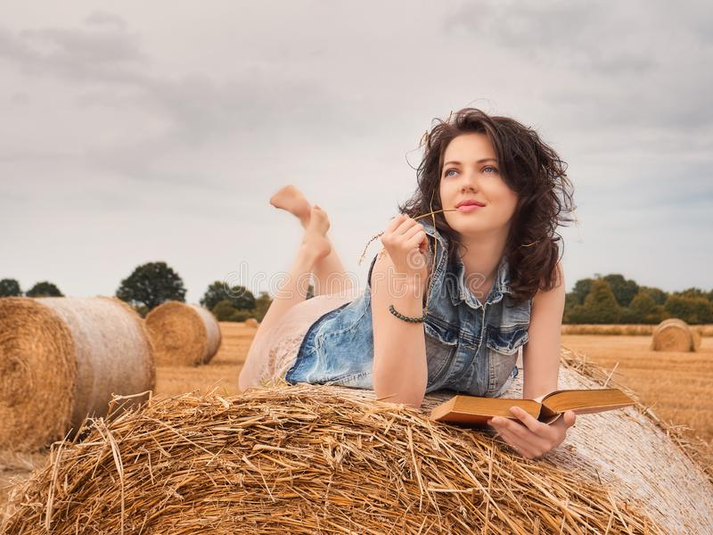 Beautiful Woman Reading book on a haystack, nature background stock photography