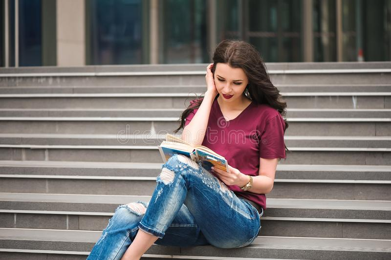 Beautiful woman reading a book on the steps of the building royalty free stock photo
