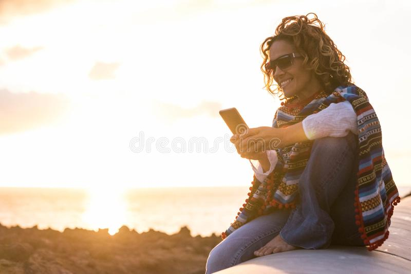 beautiful woman reading message on mobile phone in vacation during golden hour stock photography