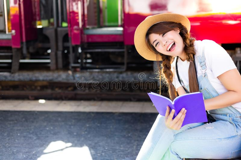 Beautiful woman is reading travel guide book for looking tourist stock photos