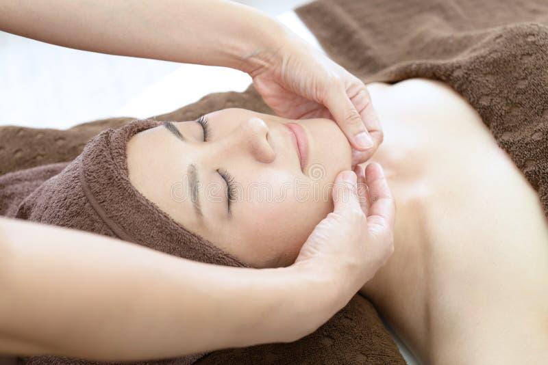 Beautiful woman receiving facial massage stock photos
